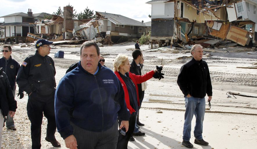 FILE - In this Nov. 2, 2012 file photo, New Jersey Gov. Chris Christie, third from left, walks past damaged homes along the Atlantic Ocean in Mantoloking, N.J. after Superstorm Sandy hit the area on Oct. 29, 2012. The third anniversary of Superstorm Sandy's landfall and destruction on the coasts of New York and New Jersey is Thursday, Oct. 29, 2015, and some victims are still not back in homes that were pummeled by the storm. (AP Photo/Mel Evans, Pool, File)