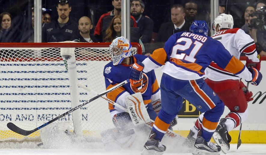New York Islanders goalie Thomas Greiss (1), of Germany, looks over his shoulder as Carolina Hurricanes defenseman Ron Hainsey (65) scores the winning goal past the defense of Islanders right wing Kyle Okposo (21) in overtime of an NHL hockey game in New York, Thursday, Oct. 29, 2015.  The Hurricanes defeated the Islanders 3-2. (AP Photo/Kathy Willens)