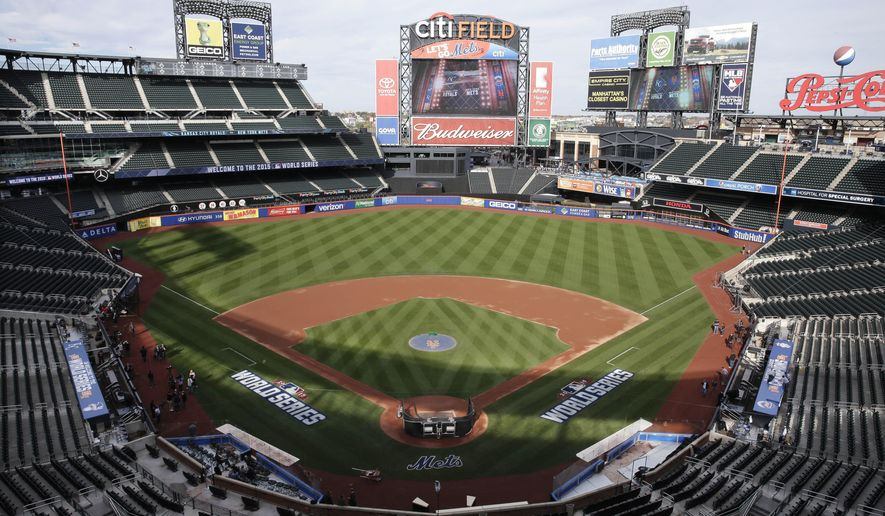 Members of the media and grounds crew work on the field at Citi Field in New York, Thursday, Oct. 29, 2015. The New York Mets are to face the Kansas City Royals in Game 3 of the World Series at the stadium on Friday. (AP Photo/Peter Morgan)