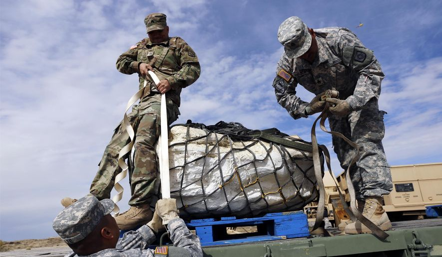Sgt. 1st Class Terrill Lee, from left, Sgt. James Ray and Staff Sgt. Noe Amador, secure the remains of a Pentaceratops, Thursday, Oct. 29, 2015, in the Bisti-De-Na-Zin Wilderness area south of Farmington, N.M. The fossils are encapsulated in heavy plaster jackets. They're being trucked to the New Mexico Museum of Natural History and Science in Albuquerque. (Jon Austria/The Daily Times via AP) MANDATORY CREDIT