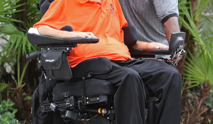 In this photo taken Friday, Oct. 23, 2015, Marc Buoniconti, left, and Herman Jacobs pose for a photo in Coconut Grove, Fla. Buoniconti, who played for the Citadel, was paralyzed in a college football game 30 years ago when he tackled Jacobs, an East Tennessee State fullback.  Among those Marc has inspired was Jacobs, who was emotionally paralyzed for years after Marc's injury. When Marc heard about his troubles he encouraged him to shed the guilt. He brought Jacobs to Miami, where they were roommates while Herman studied to be a chef.  (Walter Michot/The Miami Herald via AP)  MAGS OUT; MANDATORY CREDIT