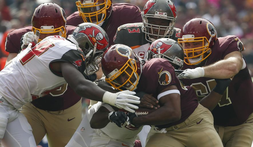 ADVANCE FOR SUNDAY, NOV. 1 AND THEREAFTER - In this photo taken Oct. 25, 2015, Washington Redskins running back Alfred Morris (46) is stopped by the Tampa Bay Buccaneers defense during the first half of an NFL football game in Landover, Md. In their actions and their words at the outset of this season, new general manager and second-year head coach Jay Gruden made quite clear that they wanted the Washington Redskins to be a run-first team. And they did, indeed, begin things that way, becoming the first NFL club in nearly a decade to have a pair of guys each rush for 100 yards in Weeks 1 and 2.(AP Photo/Alex Brandon)