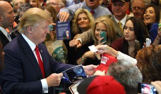 Republican presidential candidate Donald Trump signs autographs after speaking during a rally at the Nugget Convention Center in Sparks Nev., Thursday, Oct. 29, 2015. (AP Photo/Lance Iversen) ** FILE **