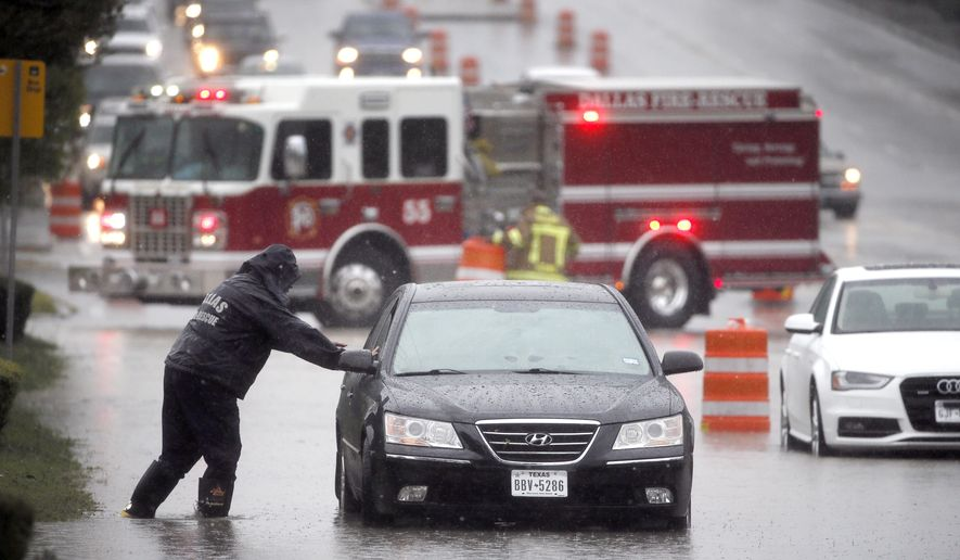 FILE - In this Oct. 23, 2015 file photo, a Dallas Fire Rescue responder makes his way over to a stalled vehicle to check on the driver, in Dallas. The vehicle stalled after the road quickly flooded during a heavy rain fall. Heavy rains this month across much of Texas have significantly improved drought conditions in the state. The U.S. Drought Monitor map on Thursday, Oct. 29, 2015, shows Texas with no areas in either extreme or exceptional drought, the two worst categories. (AP Photo/Tony Gutierrez, File)