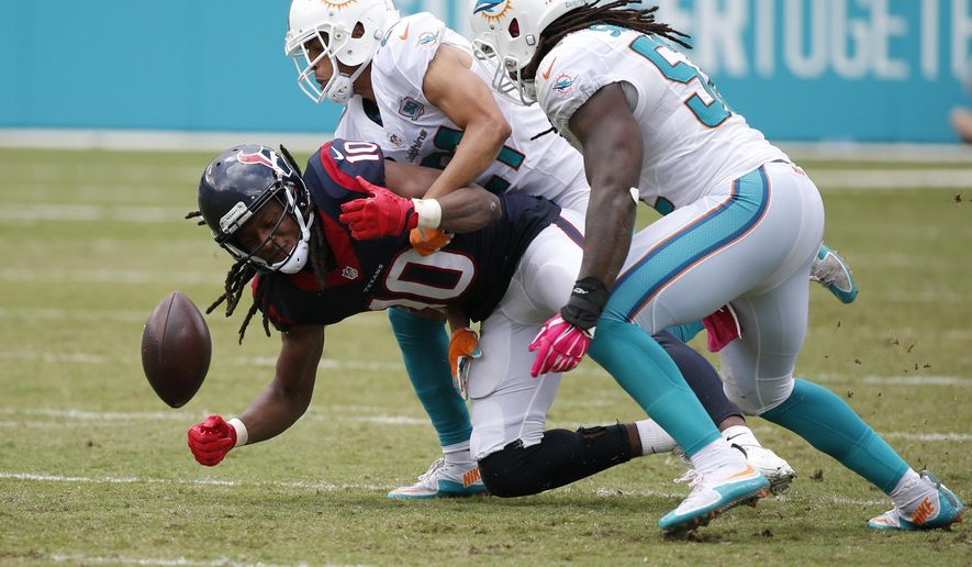 Miami Dolphins cornerback Brent Grimes (21) and middle linebacker Kelvin Sheppard (52) put pressure on Houston Texans wide receiver DeAndre Hopkins (10), during the second half of an NFL football game, Sunday, Oct. 25, 2015 in Miami Gardens, Fla. (AP Photo/Wilfredo Lee)