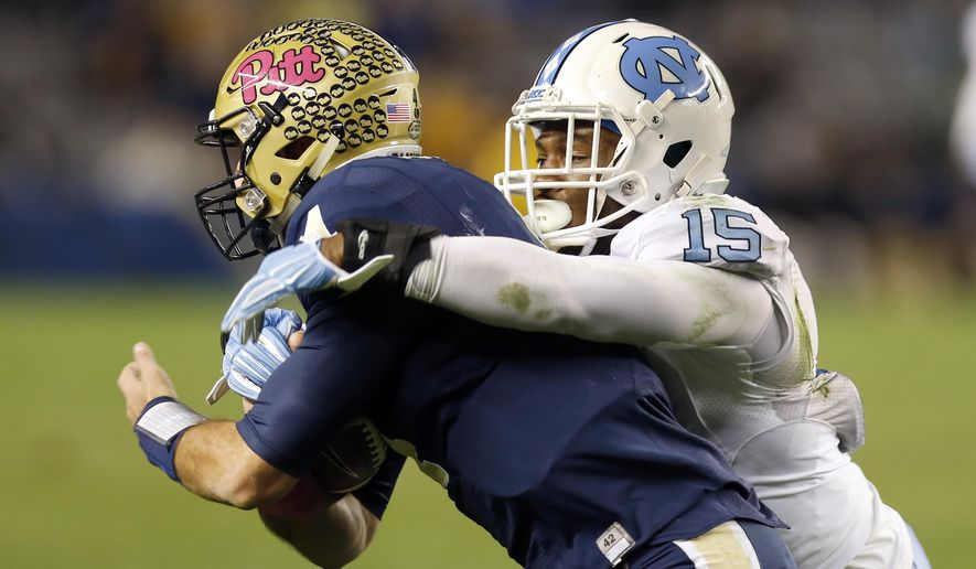 North Carolina safety Donnie Miles (15) brings down Pittsburgh quarterback Nathan Peterman (4) in the third quarter of an NCAA college football game, Thursday, Oct. 29, 2015, in Pittsburgh. North Carolina won 26-19. (AP Photo/Keith Srakocic)