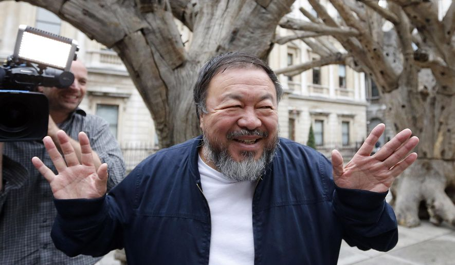 FILE - In this Tuesday, Sept. 15, 2015 file photo Chinese artist Ai Weiwei poses for photographers with one of his pieces at his exhibition at the Royal Academy of Arts in London.  Ai Weiwei is taking on Lego, brick by brick. Art galleries around the world are collecting plastic bricks for the artist after the Danish toy company refused to supply Lego for his latest project.(AP Photo/Frank Augstein, File)