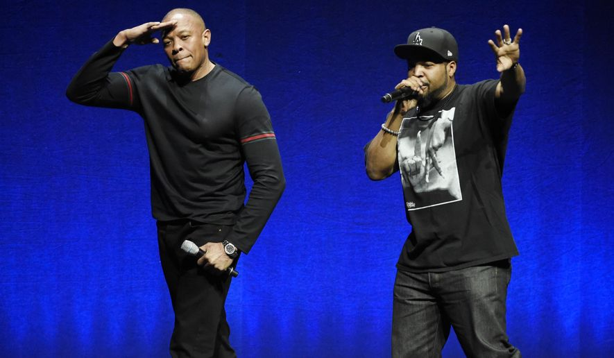"""FILE - In this April 23, 2015 file photo, N.W.A. members Dr. Dre, left, and Ice Cube, two of the subjects of the upcoming biographical drama """"Straight Outta Compton,"""" salute the crowd after speaking at the Universal Pictures presentation during CinemaCon 2015 at Caesars Palace, in Las Vegas. Jerry Heller, the former manager of N.W.A., filed a defamation lawsuit on Friday, Oct. 30, 2015, in Los Angeles against rappers Ice Cube and Dr. Dre and NBCUniversal, alleging the film """"Straight Outta Compton"""" portrayed him as a villain and has done lasting damage to his reputation. The movie released in August 2015. (Photo by Chris Pizzello/Invision/AP, File)"""