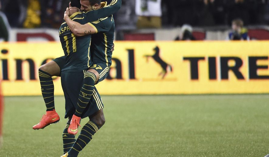 Portland Timbers midfielder Maximiliano Urruti (37) celebrates with midfielder/forward Dairon Asprilla (11) after Urruti scored a goal during overtime in an MLS playoff soccer match against Sporting Kansas City in Portland, Ore., on Thursday, Oct. 29, 2015. The Timbers won 7-6 in the shootout after a 2-2 draw. (AP Photo/Steve Dykes)