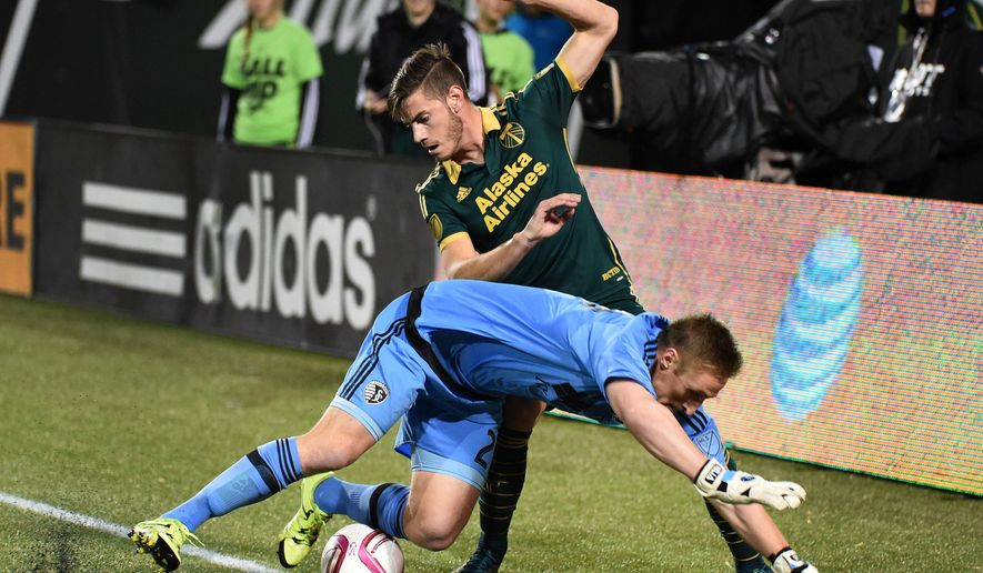 Sporting KC goalkeeper Tim Melia (29) and Portland Timbers midfielder Lucas Melano (26) go after a ball during the first half of a knockout round MLS playoff soccer match in Portland, Ore. on Thursday, Oct. 29, 2015. (AP Photo/Steve Dykes)