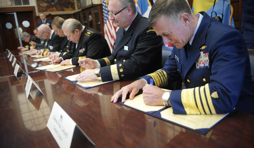 Adm. Paul Zukunft, the U.S. Coast Guard commandant, right, signs a pledge with with coast guard leaders from Arctic nations to cooperation in northern seas, Friday, Oct. 30, 2015, in New London, Conn. (AP Photo/Jessica Hill)