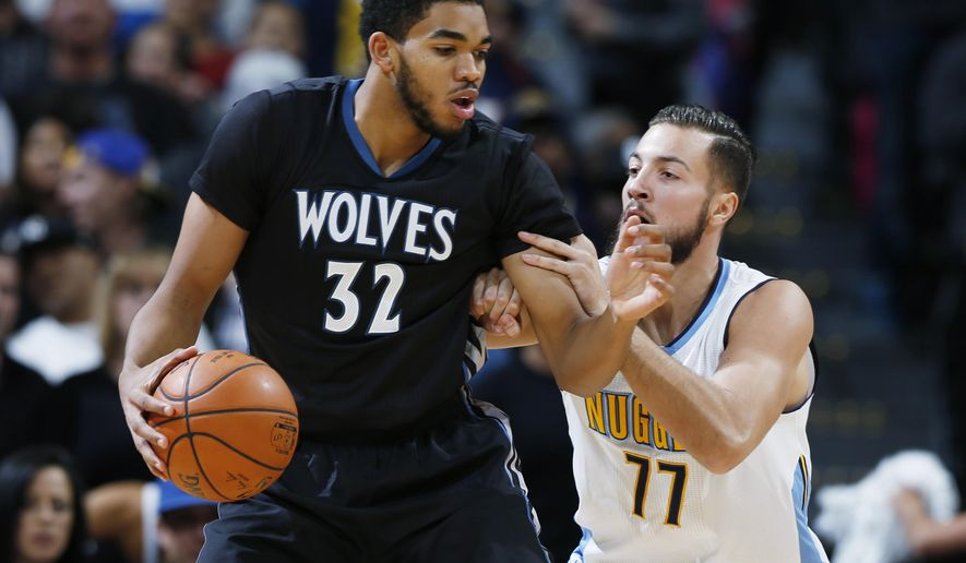 Minnesota Timberwolves center Karl-Anthony Towns, left, is tied up by Denver Nuggets forward Joffrey Lauvergne, of France, during the first half of an NBA basketball game Friday, Oct. 30, 2015, in Denver. (AP Photo/David Zalubowski)