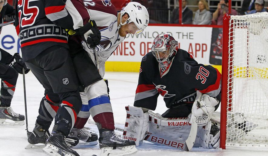 Colorado Avalanche's Gabriel Landeskog, center, of Sweden, has his shot bounce off Carolina Hurricanes goalie Cam Ward (30) during the first period of an NHL hockey game, Friday, Oct. 30, 2015, in Raleigh, N.C. (AP Photo/Karl B DeBlaker)