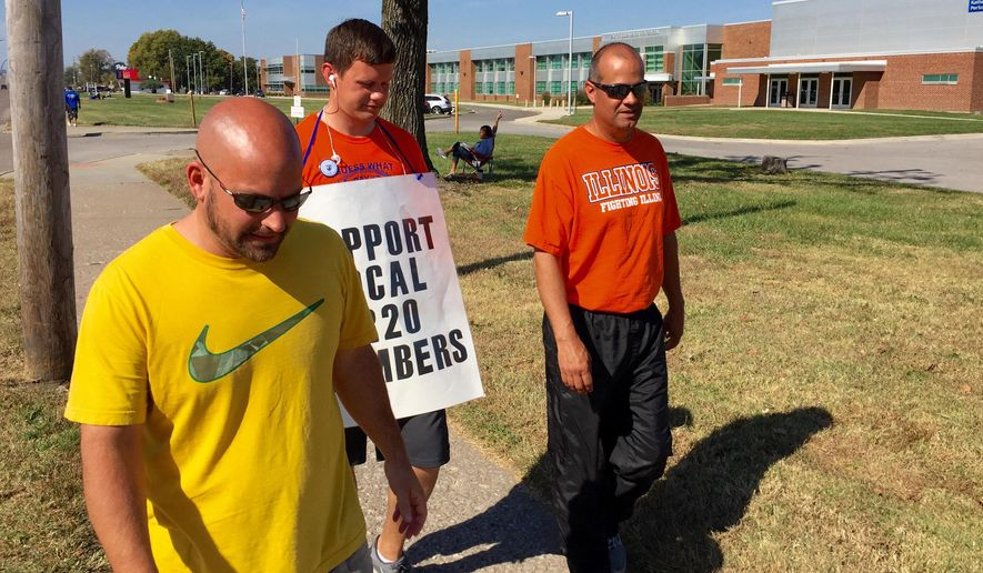FILE - In this Oct. 27, 2015 file photo striking East St. Louis teachers, from left, Jeff Schneider, Josh Cummins and Paul Thies  walk the picket line in front of East St. Louis Senior High School in East St. Louis, Ill.  In a statement released Friday Oct. 30, 2015, superintendent Arthur R. Culver said a tentative deal has been reached between East St. Louis School District 189 and the union representing hundreds of teachers who have been on strike for a month. (Steve Nagy/Belleville News-Democrat, via AP)