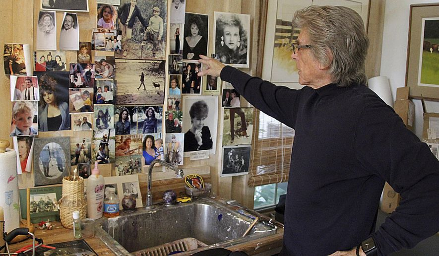 In this Sept. 11, 2015  photo, artist Tom Heflin points to photos of his children, family and friends who give him inspiration, at his studio in Winnebago, Ill. (Kimberly Watley/Rockford Register Star via AP)  MANDATORY CREDIT