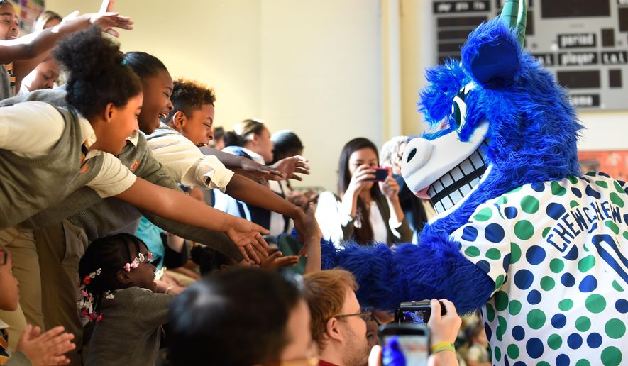 Students at Capital Preparatory Magnet School reach out to touch Chew Chew, one of the two official mascots for the Hartford Yard Goats Baseball Club, at an event at the school in Hartford, Conn., Friday, Oct. 31, 2015. Chew Chew and Chompers were introduced at a rally in the school's gymnasium. The Goats are a Double-A minor league baseball team that will begin play in the Eastern League in 2016 when the New Britain Rock Cats relocate to Hartford. (Cloe Poisson/Hartford Courant via AP) MANDATORY CREDIT