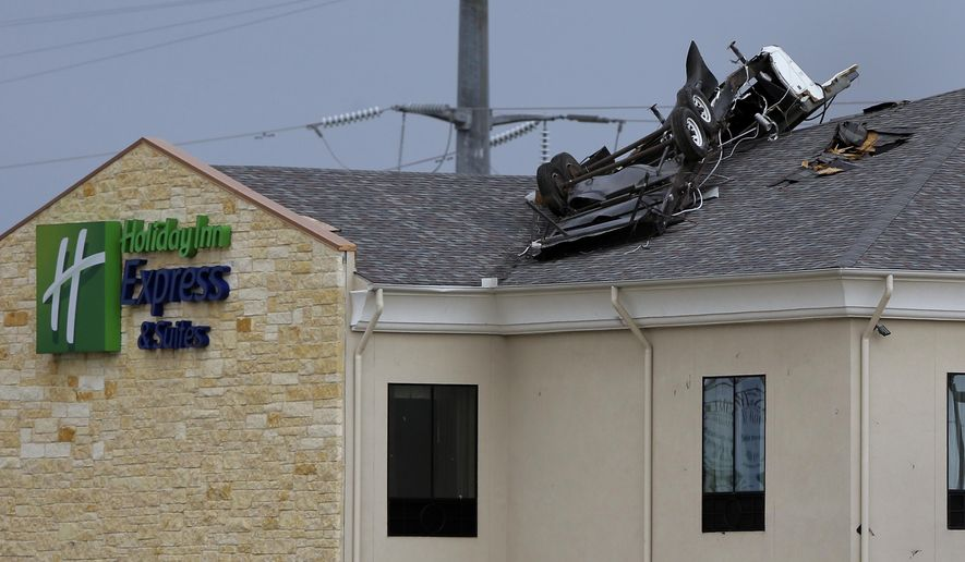 A vehicle rests on top of a three-story hotel after a tornado touched down in the area, Friday, Oct. 30, 2015, in Floresville, Texas. A fast-moving storm packing heavy rain and destructive winds overwhelmed rivers and prompted evacuations Friday in the same area of Central Texas that saw devastating spring floods. (AP Photo/Eric Gay)