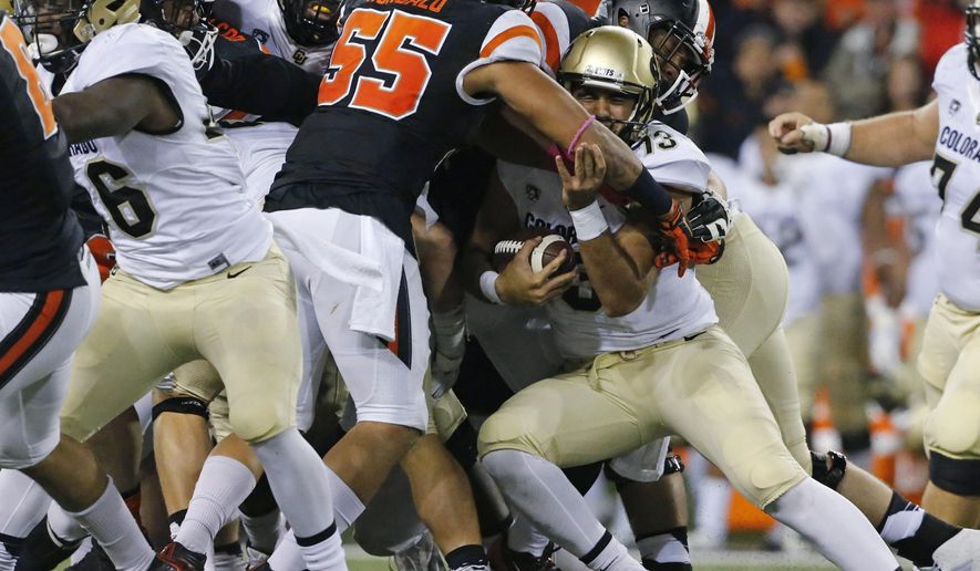 Colorado quarterback Sefo Liufau, right, is stopped by the Oregon State defense on a third down during the second half of an NCAA college football game in Corvallis, Ore., on Saturday, Oct. 24, 2015. Colorado won 17-13. (AP Photo/Timothy J. Gonzalez)