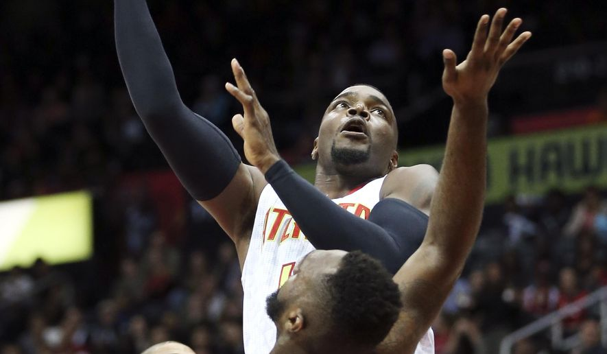 Atlanta Hawks forward Paul Millsap (4) takes a shot against Charlotte Hornets guard P.J. Hairston (19) in the first half of an NBA basketball game  Friday, Oct. 30, 2015, in Atlanta.  (AP Photo/ John Bazemore)