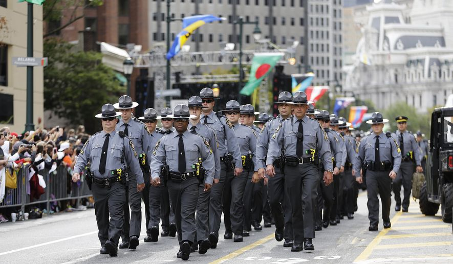 ADVANCE FOR SATURDAY, OCT. 31, 2015 - FILE - In this file photo taken Sept. 26, 2015, Pennsylvania State Police troopers walk up the Benjamin Franklin Parkway in Philadelphia as Pope Francis visits the city. An analysis by the Tribune-Review of Greensburg, Pa., and Pittsburgh examined staffing data from 2008 to 2014 for 89 Pennsylvania State Police stations, and found a 17 percent decrease in officers assigned to regional stations that conduct patrols, investigate crime and handle calls, and decreased staffing at 75 percent of the stations despite about 1,200 troopers graduating from the state police academy. (AP Photo/David Goldman, File)