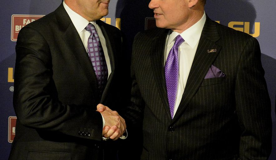 FILE - In this Jan. 14, 2015, file photo, LSU defensive coordinator Kevin Steele, left, shakes hands with LSU head coach Les Miles during a news conference in Baton Rouge, La. After Steele's difficult final year as defensive coordinator at Clemson, it wasn't long before he was back on another staff with Nick Saban at Alabama. So Saban counts himself among the least surprised to see Steele and his new defense thriving at LSU in advance of their matchup with the Crimson Tide.  (AP Photo/Hilary Scheinuk, File)