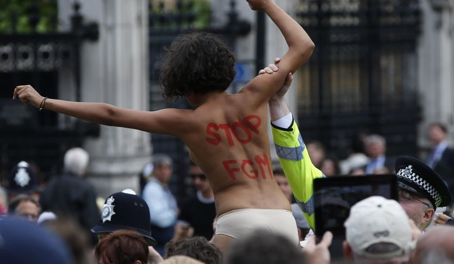 FILE - In is Monday, July 7, 2014 file photo, a British police officer arrests an activist from FEMEN group as she shouts slogans against female genital mutilation during a protest opposite the Houses of Parliament in central London. A new law requiring professionals to report cases of female genital mutilation to police for those under 18 is being introduced in England and Wales, but some opponents of the practice warn the law could make girls reluctant to seek medical care. The law taking effect Saturday, Oct. 31, 2015 makes it a crime not to notify police when health care workers, social workers or teachers see someone under 18 who has had their genitals removed or damaged for non-medical reasons. (AP Photo/Lefteris Pitarakis, File)
