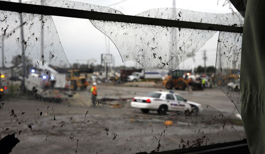 Emergency workers are seen through a broken window after severe weather passed the area, Friday, Oct. 30, 2015, in Floresville, Texas.  A fast-moving storm packing heavy rain and destructive winds overwhelmed rivers and prompted evacuations Friday in the same area of Central Texas that saw devastating spring floods.  (AP Photo/Eric Gay)