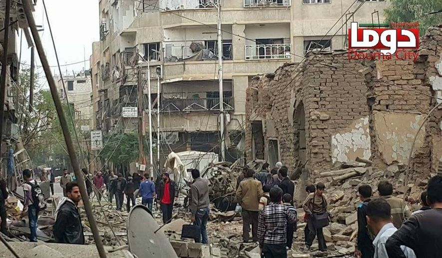 In this photo provided by the Syrian anti-government activist group Douma Revolution, which has been authenticated based on its contents and other AP reporting, people gather near damaged buildings, in the aftermath of an airstrike that activists said was carried out by Russia, in Douma, Syria, Thursday, Oct. 29, 2015. (Douma Revolution via AP)