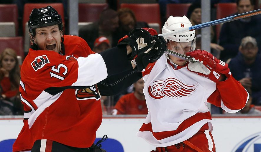 Ottawa Senators center Zack Smith (15) and Detroit Red Wings left wing Justin Abdelkader (8) battle for position in the first period of an NHL hockey game Friday, Oct. 30, 2015 in Detroit. (AP Photo/Paul Sancya)