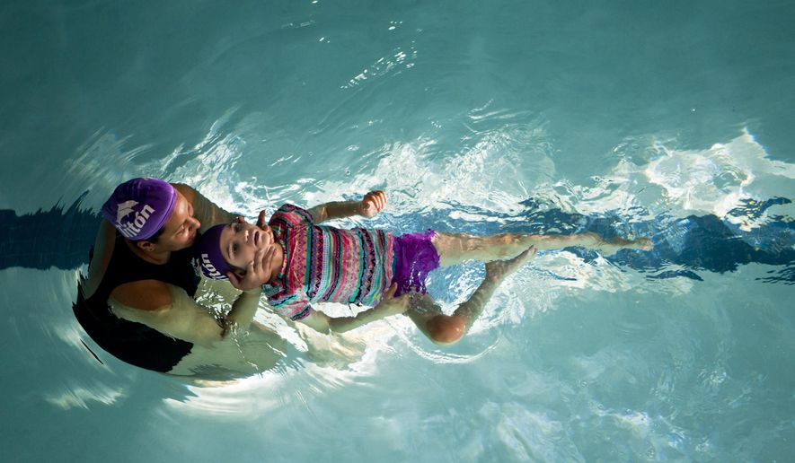 Graciela Elizalde, an 8-year-old who suffers from Lennox-Gastaut syndrome, a severe form of epilepsy that causes intense seizures, receives hydrotherapy treatment at a swimming complex in Monterrey, Mexico, Thursday, Oct. 29, 2015. Elizalde's parents have already seen a difference in their daughter since she began taking a marijuana extract recently. A federal judge gave them permission to import the marijuana oil. (AP Photo/Esteban Felix)