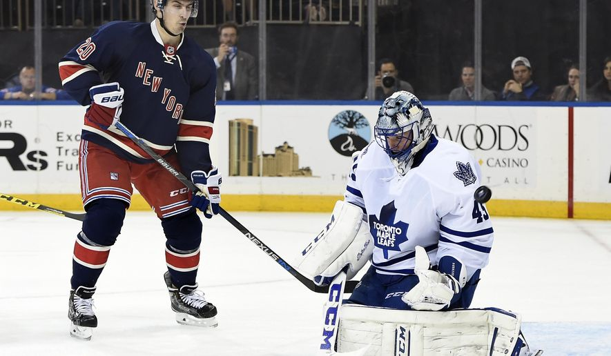 New York Rangers left wing Chris Kreider (20) watches Toronto Maple Leafs goalie Jonathan Bernier (45) deflect a puck away from the goal during the second period of an NHL hockey game on Friday, Oct. 30, 2015, in New York. (AP Photo/Kathy Kmonicek)