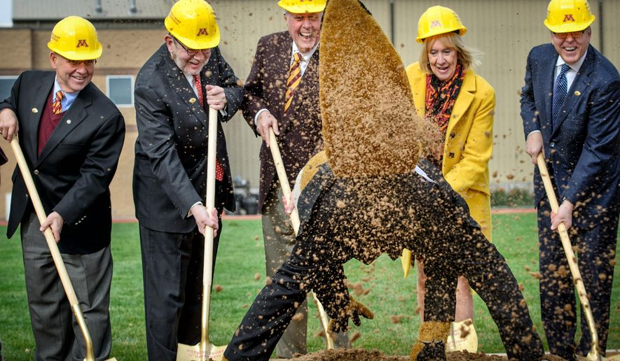 """University of Minnesota mascot """"Goldy Gopher"""" throws dirt towards photographers at groundbreaking ceremonies for the """"athletes village"""" Friday, Oct. 30, 2015, at the University of Minnesota in Minneapolis. From left, taking part in the ceremonies are regent Dean Johnson, University President Eric Kaler, benefactor and volunteer John Lindahl, his wife Nancy, and Chris Policinski, CEO of Land O'Lakes, Inc. (Glen Stubbe/Star Tribune via AP)  MANDATORY CREDIT; ST. PAUL PIONEER PRESS OUT; MAGS OUT; TWIN CITIES LOCAL TELEVISION OUT"""