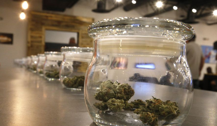 In this Sept. 16, 2015 file photo, marijuana for sale is kept in jars for customers to sample smells, on opening day of a new outlet of the Colorado Harvest Company recreational marijuana stores, in Aurora, Colo. (AP Photo/Brennan Linsley, File)