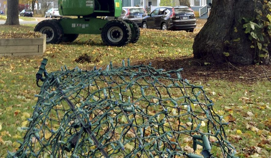 One of six diamond-shaped sculptures that will be erected and illuminated in memory of six apartment house fire victims, foreground, awaits installation on Friday, Oct. 30, 2015, in a park near the site of the apartment house fire in Portland, Maine. The memorial will be unveiled when friends, family and neighbors gather on Sunday, the first anniversary of the deadly blaze. (AP Photo/David Sharp)