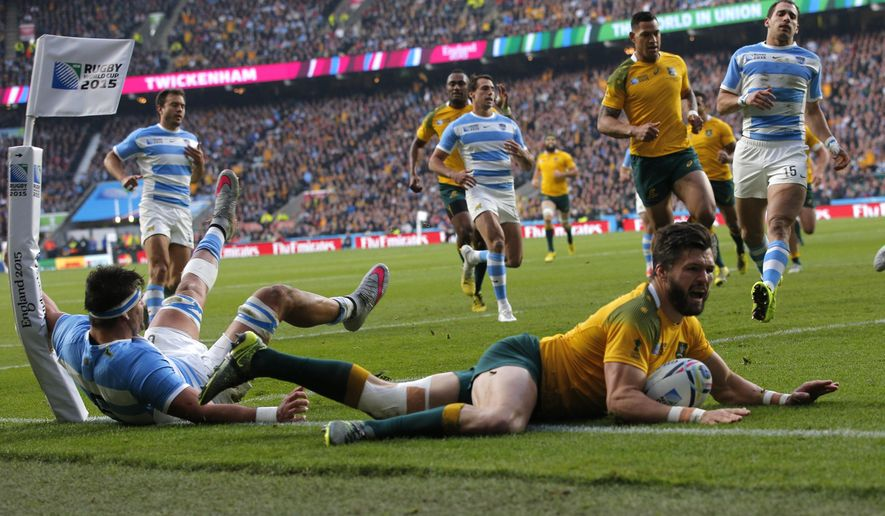 Australia's Adam Ashley-Cooper, right, dives over to score a try as Argentina's Pablo Matera attempts to tackle during their Rugby World Cup semifinal match at Twickenham Stadium, London, Sunday, Oct. 25, 2015. (AP Photo/Christophe Ena)