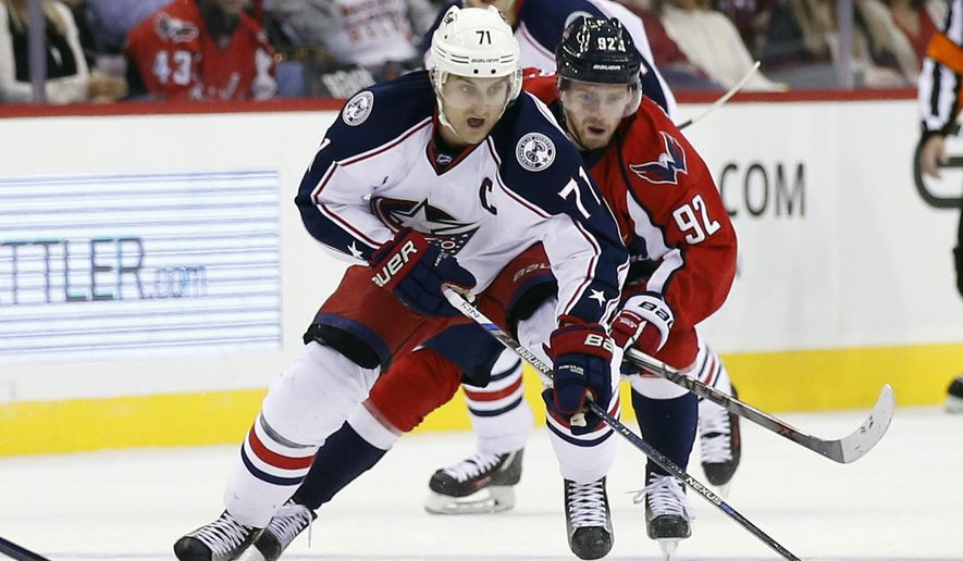 CORRECTS TO SECOND PERIOD NOT FIRST PERIOD - Columbus Blue Jackets left wing Nick Foligno (71) skates with the puck as Washington Capitals center Evgeny Kuznetsov (92), from Russia, pursues in the second period of an NHL hockey game, Friday, Oct. 30, 2015, in Washington. (AP Photo/Alex Brandon)