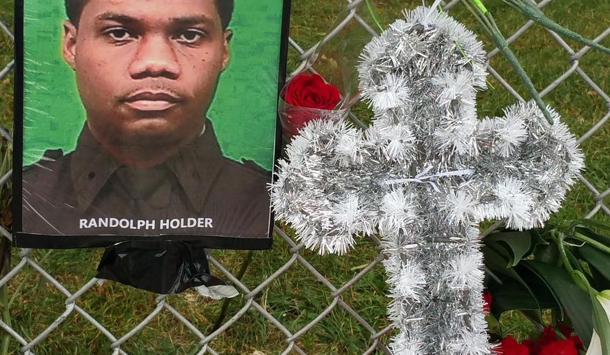 """A memorial honoring slain NYPD Officer Randolph Holder is attached to a fence of the Wagner housing project in New York, Sunday, Oct. 25, 2015, across the FDR Drive from where a search earlier in the morning ended with the discovery of the gun police believe was used to kill him. A gun was found in the Harlem River during a round-the-clock investigation, following the killing of Holder on Oct. 20.  Police said that around 3 a.m. divers recovered a gun from the river """"consistent"""" with the weapon used to kill Holder during a foot chase. (AP Photo/Verena Dobnik)"""