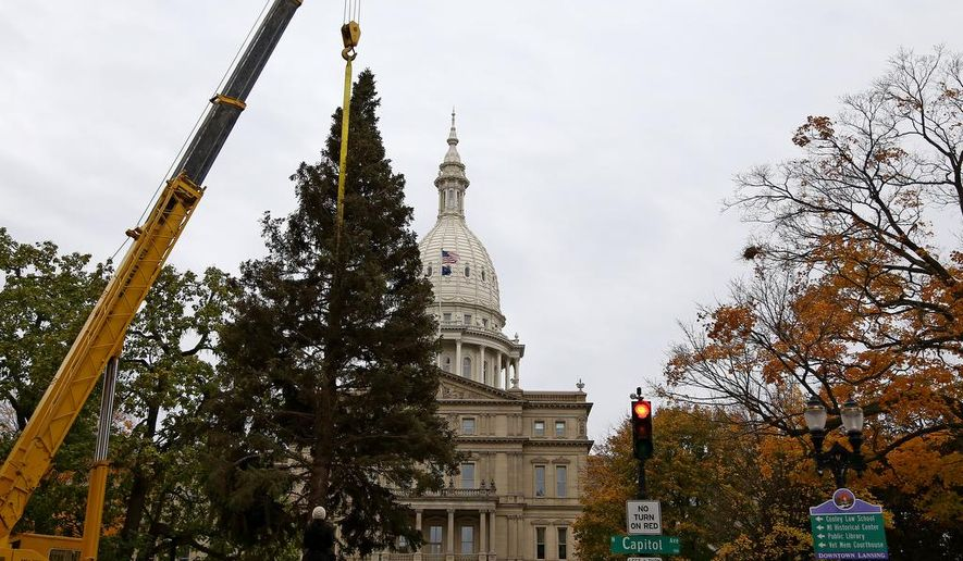 A christmas tree is delivered outside the State Capitol building in Lansing, Mich., Saturday morning, Oct. 31, 2015. (Danielle Duval/MLive.com via AP)  ALL LOCAL TELEVISION OUT; LOCAL TELEVISION INTERNET OUT; MANDATORY CREDIT