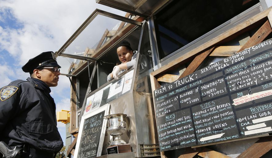 "Snowday staffer Marivette Alicea, 25, right, discusses the food truck's ""gourmet lumberjack"" menu with a New York city police officer as he decides what to order during Smorgasburg at Brooklyn's Grand Army Plaza, Sunday, Oct. 18, 2015, in New York. The truck is part of the nonprofit Drive Train program that prepares formerly incarcerated youth to re-enter the job market. They're taught to cook, plus hospitality, money management and even emotional development. (AP Photo/Kathy Willens)"