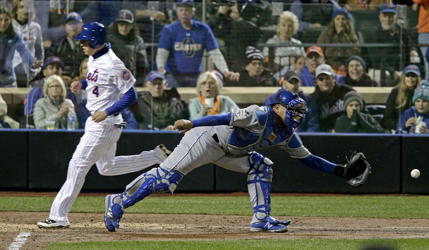 New York Mets' Wilmer Flores, right, scores past Kansas City Royals catcher Salvador Perez on a sacrifice fly ball by Curtis Granderson during the third inning of Game 4 of the Major League Baseball World Series Saturday, Oct. 31, 2015, in New York.(AP Photo/Peter Morgan)