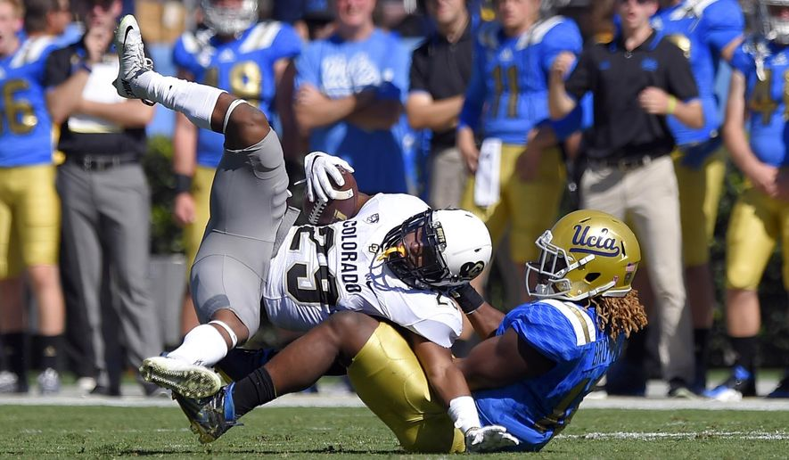 Colorado wide receiver Donovan Lee, left, is tackled by UCLA linebacker Jayon Brown during the first half of an NCAA college football game, Saturday, Oct. 31, 2015, in Pasadena, Calif. (AP Photo/Mark J. Terrill)