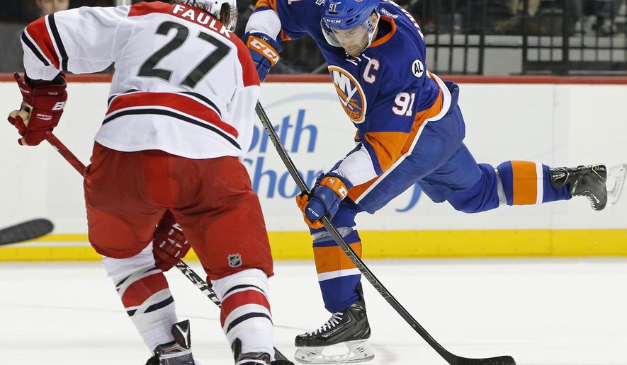 New York Islanders center John Tavares (91) shoots on goal with Carolina Hurricanes defenseman Justin Faulk (27) defending in overtime of an NHL hockey game in New York, Thursday, Oct. 29, 2015. The Hurricanes defeated the Islanders 3-2. (AP Photo/Kathy Willens)