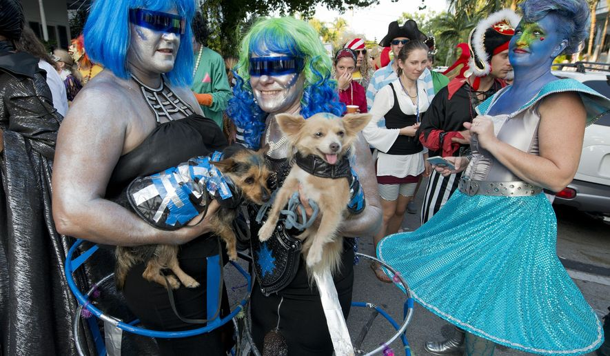 "In this Friday, Oct. 30, 2015, photo provided by the Florida Keys News Bureau, people and their dogs dresses as space creatures proceed down Fleming Street in Key West, Fla., during the Fantasy Fest Masquerade March. Thousands participated in the event that was one of the highlights of the subtropical island's annual Fantasy Fest costuming and masking festival that is to conclude Sunday, Nov. 1. This year's festival theme is ""All Hallows Intergalactic Freak Show."" (Andy Newman/Florida Keys News Bureau via AP)"
