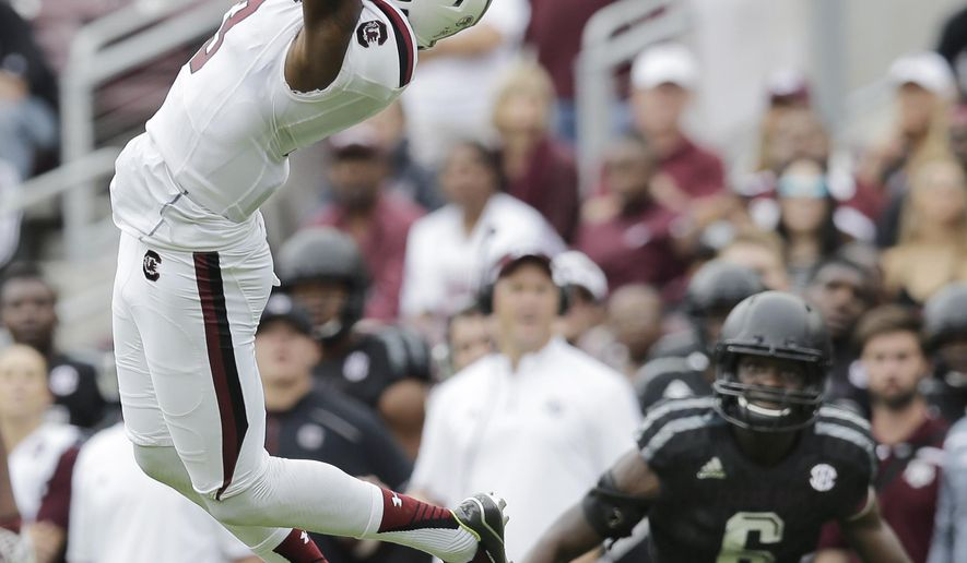 South Carolina wide receiver D.J. Neal, left, catches a pass as Texas A&M wide receiver Christian Kirk (3) looks on during the first half of an NCAA college football game, Saturday, Oct. 31, 2015, in College Station, Texas. (AP Photo/Eric Gay)