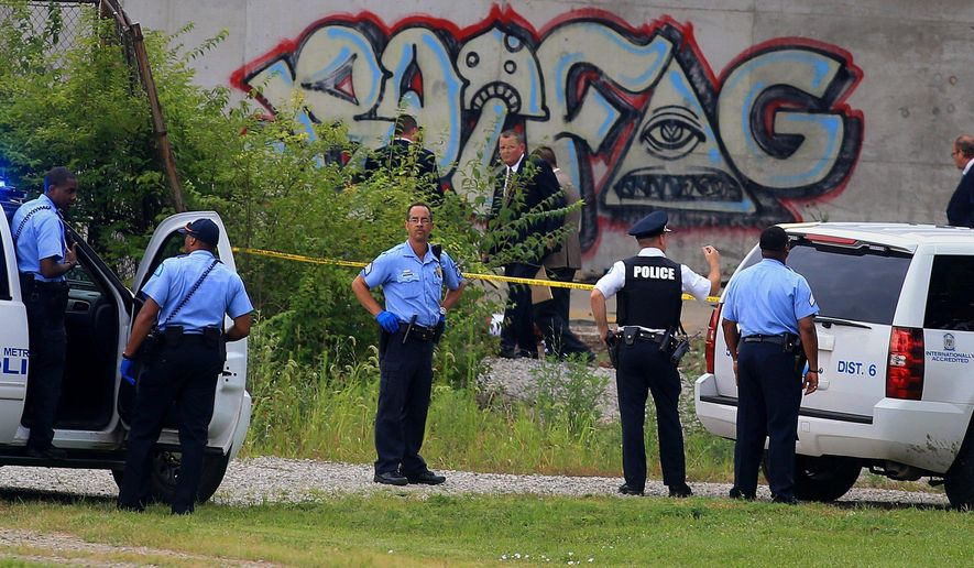 In this photo made July 20, 2015, St. Louis police investigate a homicide scene in St. Louis. Each of Missouri's big cities, St. Louis and Kansas City, have had more homicides by mid-October of this year than in all of 2014, evidence, experts say, of the uphill battle to make urban streets safe.  (Christian Gooden/St. Louis Post-Dispatch via AP)  EDWARDSVILLE INTELLIGENCER OUT; THE ALTON TELEGRAPH OUT; MANDATORY CREDIT