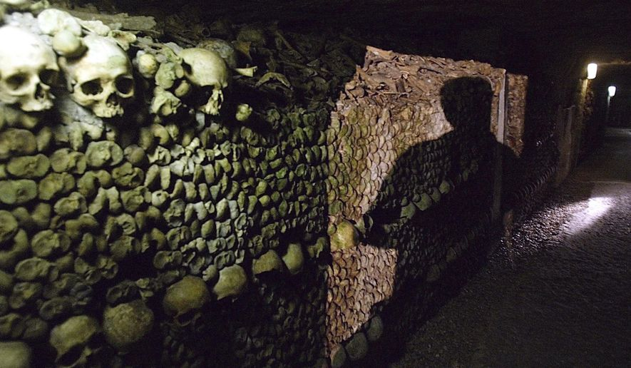 FILE - In this  Sept.15, 2004 file photo, a man is shadowed in the catacombs, in Paris. The City of Light harbors a vast network of subterranean tunnels that once gave refuge to bandits, smugglers and saints and cradles the remains of some 6 million Parisians. The Catacombs form a dark, 200-mile (322 kilometer) underground labyrinth beneath the City of Light.  (AP Photo/Michel Euler,file)