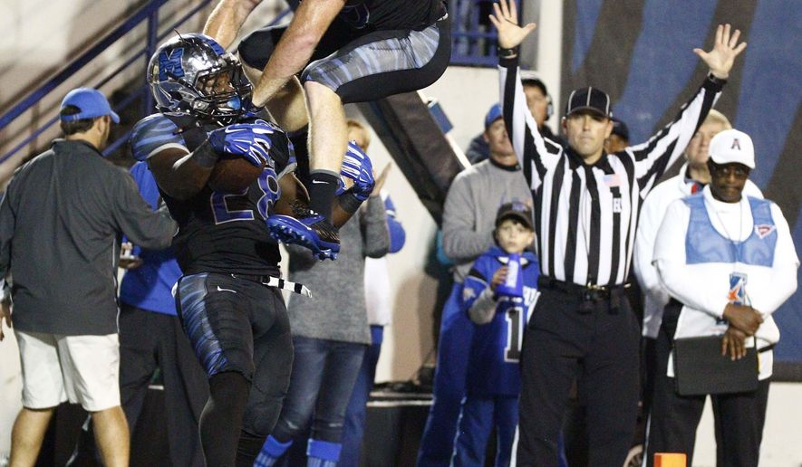 Memphis tight end Alan Cross (40) leaps in the air to celebrate running back Doroland Dorceus' (28) touchdown against Tulane in the first half of an NCAA college football game in Memphis, Tenn., Saturday, Oct. 31, 2015. (AP Photo/Rogelio V. Solis)