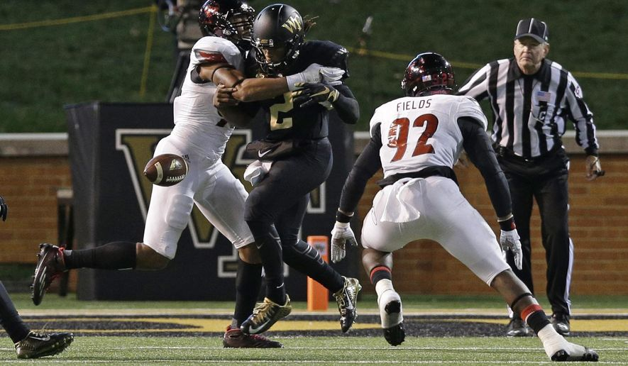 Wake Forest's Kendall Hinton (2) fumbles the ball as he is hit by Louisville's Trevon Young (91) as Devonte Fields (92) closes in during the second half of an NCAA college football game in Winston-Salem, N.C., Friday, Oct. 30, 2015. Louisville won 20-19. (AP Photo/Chuck Burton)