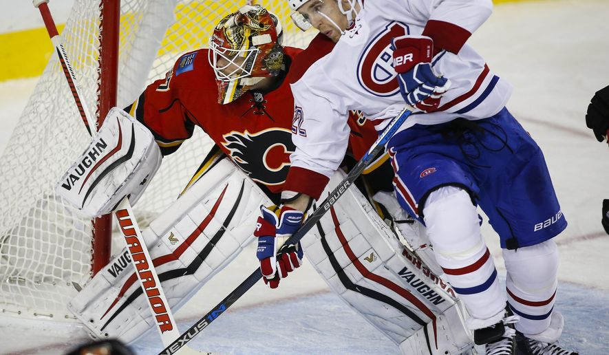 Montreal Canadiens' Dale Weise, right, is checked into Calgary Flames' goalie Joni Ortio, from Finland, during the second period of an NHL hockey game Friday, Oct. 30, 2015, in Calgary, Alberta. (Jeff McIntosh/The Canadian Press via AP) MANDATORY CREDIT