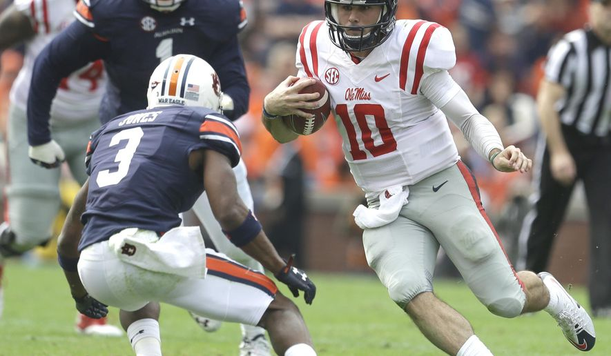 Mississippi quarterback Chad Kelly (10) scrambles for yardage as he tries to get by Auburn defensive back Jonathan Jones (3) during the first half of an NCAA college football game, Saturday, Oct. 31, 2015, in Auburn, Ala. (AP Photo/Butch Dill)